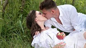 Картинка Влюбленные пары Мужчина Яблоки Трава Целует 2 Шатенка Свидание Девушки