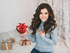 Фотографии Новый год Шатенка Улыбка Подарки Смотрит Свитер Девушки