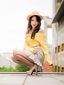 Картинка Азиатка Размытый фон Сидя Юбка Блузка Шляпа Шатенки Смотрят молодые женщины