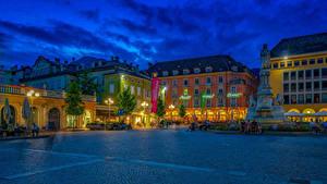 Картинка Италия Здания Вечер Памятники Городской площади Уличные фонари Деревьев Bolzano Trentino город