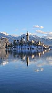 Картинки Словения Озеро Горы Замки Зима Альпы Снег Lake Bled, Bled castle