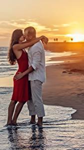 Обои Рассветы и закаты Любовники Мужчины Пляжи 2 Обнимает Целоваться Свидание молодые женщины