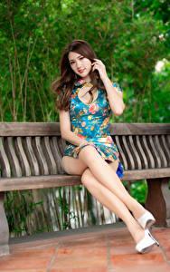 Обои для рабочего стола Азиаты Шатенка Скамейка Сидит Ноги Платья Смотрят Красивая девушка