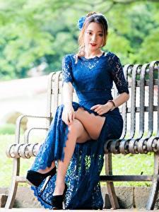 Картинки Азиатка Размытый фон Скамья Шатенки Платье Сидящие Руки Ноги Туфель молодые женщины