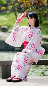Картинки Азиатки Размытый фон Брюнеток Кимоно Веер Сидит молодая женщина