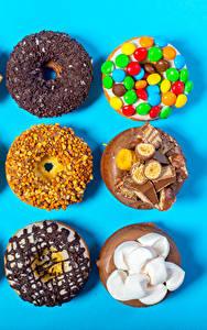 Фото Сладости Пончики Шоколад Орехи Конфеты Цветной фон Зефирки
