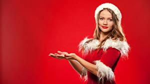 Фото Рождество Шатенка Униформа Смотрит Руки Красный фон Девушки
