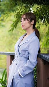 Картинки Азиатка Размытый фон Плащом Шатенки молодая женщина