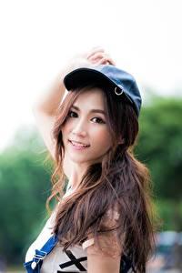 Фотография Азиатка Размытый фон Шатенки Бейсболка Взгляд Улыбается молодая женщина