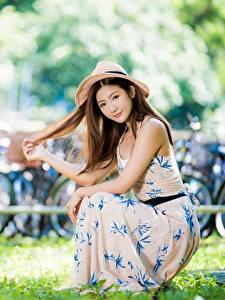 Фото Азиатки Траве Платье Шляпа Сидя Боке Шатенки Рука молодая женщина