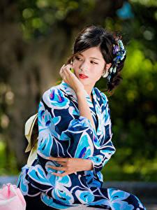 Фотографии Азиаты Размытый фон Рука Кимоно Брюнетка Сидит девушка
