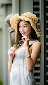 Фотографии Азиаты Размытый фон Шляпа Руки Очки молодые женщины