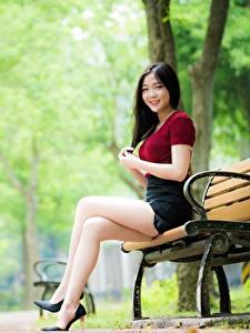 Обои для рабочего стола Азиатки Скамья Размытый фон Брюнеток Улыбается Руки Сидя Ноги Туфлях молодая женщина