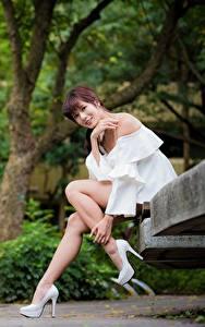 Картинки Азиатки Парк Скамейка Улыбка Взгляд Ног Красивая Сидит Шатенки Девушки