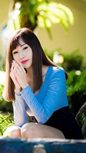 Картинки Азиатка Размытый фон Сидит Руки Позирует Шатенки девушка