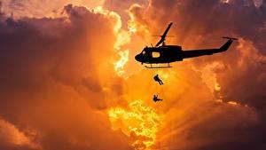 Картинка Вертолет Рассветы и закаты Десант Силуэт Лучи света Облако Американская Bell UH-1 Iroquois Авиация Армия