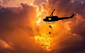 Картинка Вертолеты Рассветы и закаты Десант Силуэт Лучи света Облако Американская Bell UH-1 Iroquois Авиация Армия
