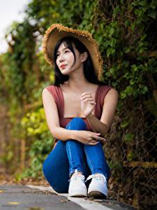Фото Азиатка Шляпа Сидя Джинсов Размытый фон Брюнетка Девушки