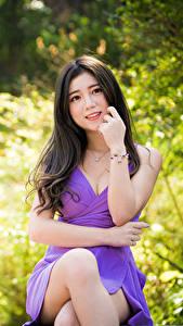Картинки Азиаты Брюнеток Сидя Платья Ноги Смотрит Размытый фон молодая женщина