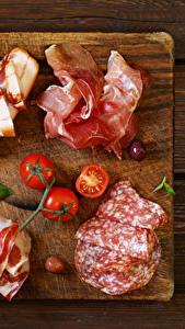 Картинки Мясные продукты Колбаса Ветчина Помидоры Разделочная доска Еда