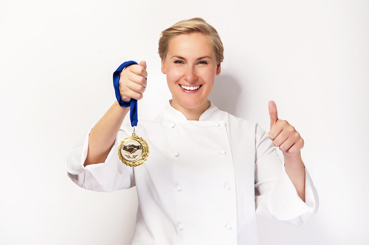 Фото Блондинка улыбается девушка Пальцы Медаль белым фоном блондинки блондинок Улыбка Девушки молодая женщина молодые женщины медали Белый фон белом фоне