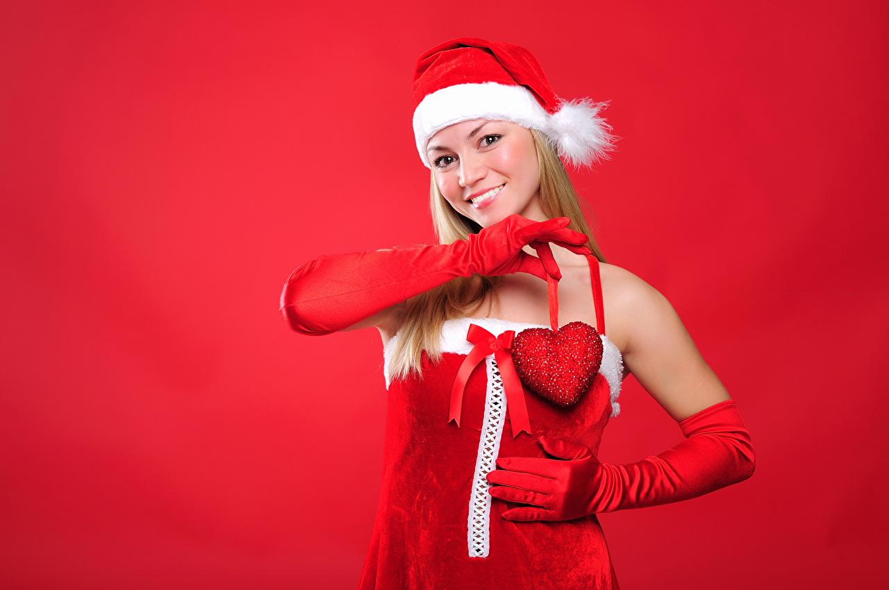 Фотографии Новый год Блондинка Улыбка Сердце Перчатки Шапки Девушки Красный фон Рождество сердечко