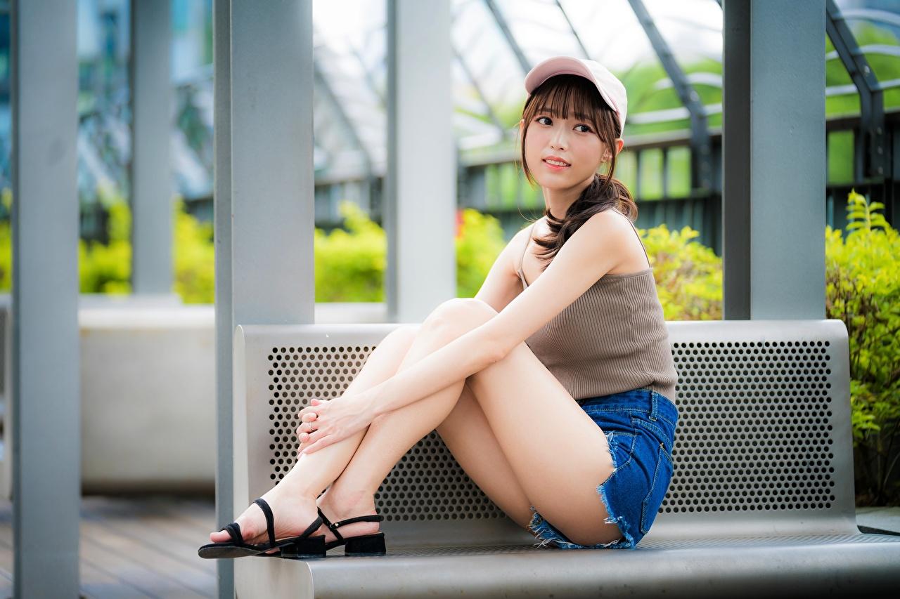 Картинка Красивые Девушки Ноги азиатка Шорты Сидит Скамья Бейсболка красивый красивая девушка молодые женщины молодая женщина ног Азиаты азиатки сидя шорт шортах сидящие Скамейка Кепка кепке кепкой