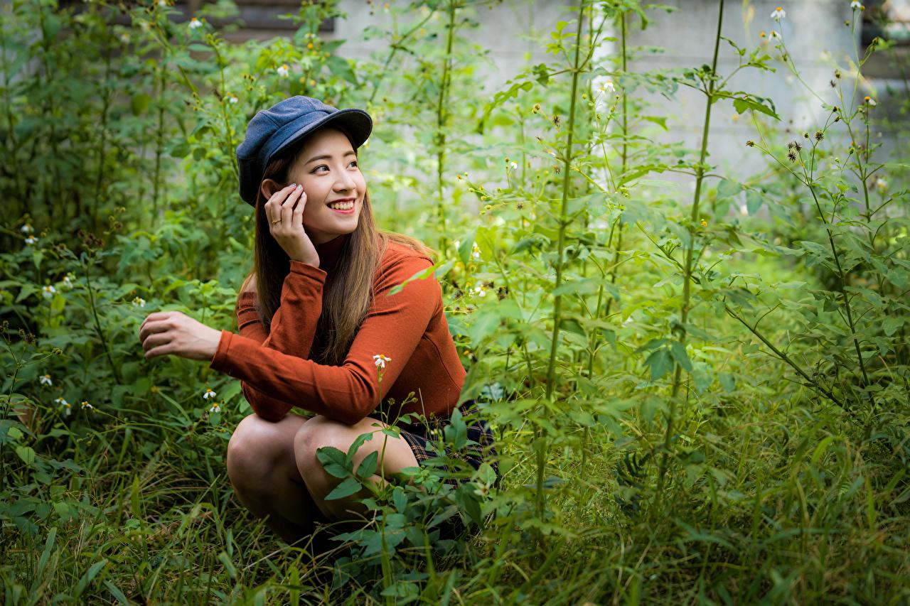 Фотография Улыбка девушка Азиаты Свитер Сидит Трава кепкой улыбается Девушки молодая женщина молодые женщины азиатки азиатка свитере свитера сидя траве сидящие кепке Кепка Бейсболка