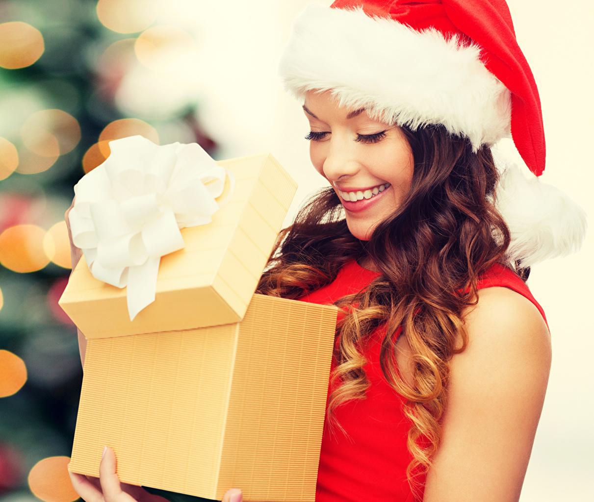 Картинка Шатенка Новый год Улыбка шапка молодые женщины подарков шатенки Рождество улыбается Шапки в шапке Девушки девушка молодая женщина Подарки подарок