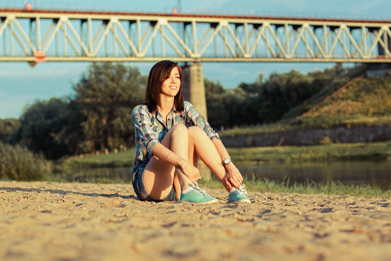 Картинка Шатенка улыбается боке Девушки Ноги песка Руки Сидит шатенки Улыбка Размытый фон девушка молодая женщина молодые женщины ног Песок песке рука сидя сидящие