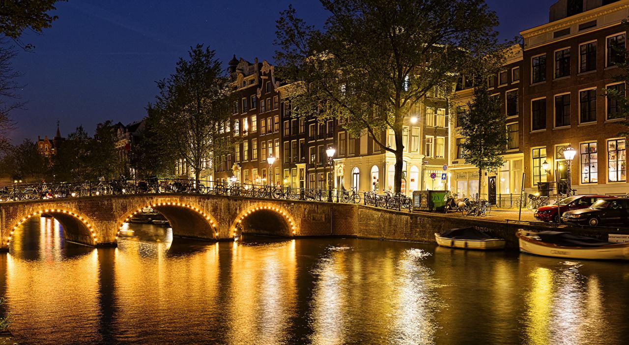 Картинка Амстердам Нидерланды Мосты Водный канал Пирсы Ночные Уличные фонари Здания Города Деревья Ночь Причалы Пристань Дома