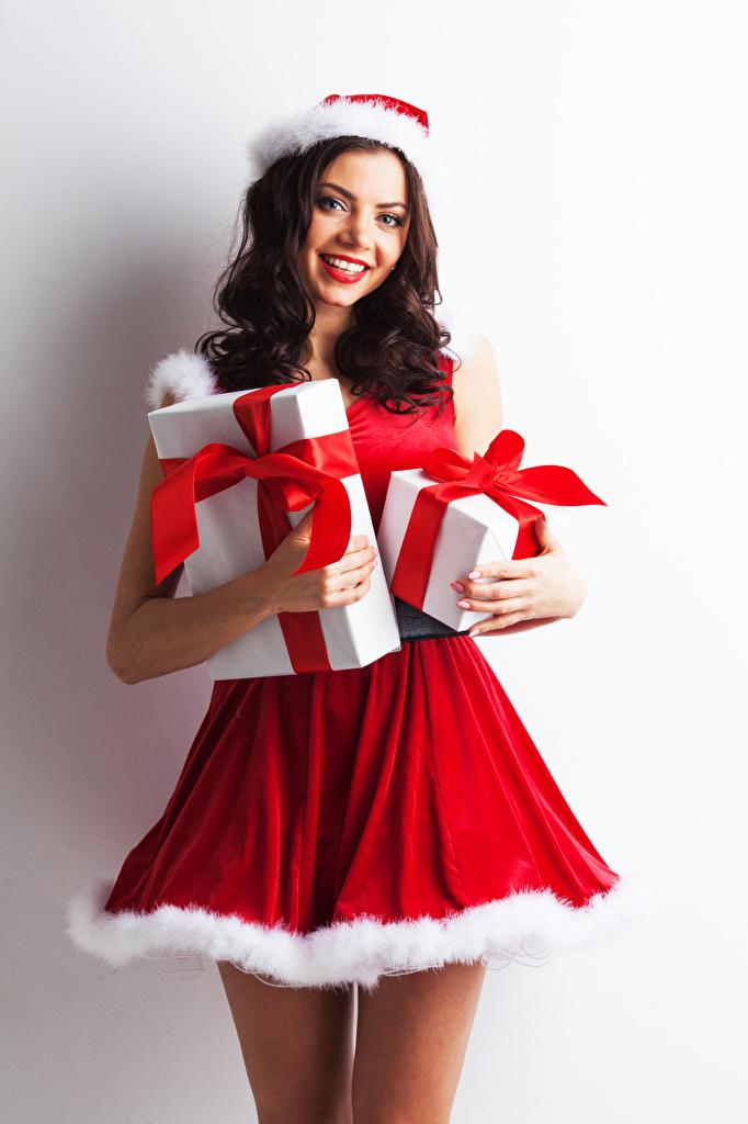 Обои Шатенка Новый год Улыбка Девушки Подарки Униформа смотрит Белый фон Рождество Взгляд