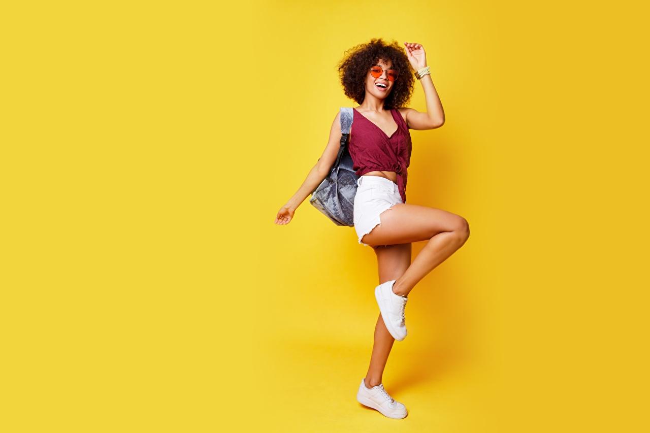 Фотография позирует девушка Ноги Майка Шорты очков Цветной фон Поза Девушки молодая женщина молодые женщины ног майки майке шорт Очки очках шортах