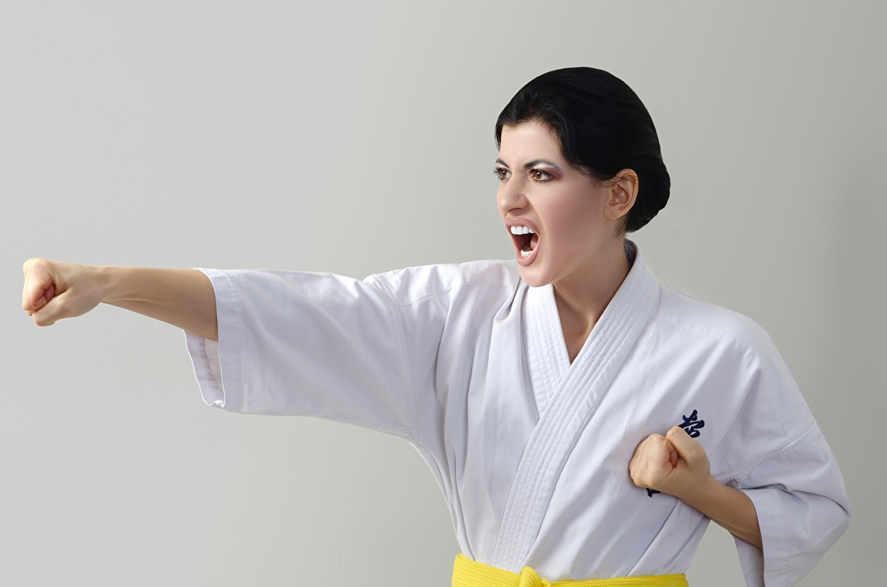 Картинки Девушки Руки Брюнетка униформе Karate Удар кричит сером фоне Кулак девушка молодая женщина молодые женщины рука брюнетки брюнеток Униформа Бьет Ударяет Крик кричат Серый фон