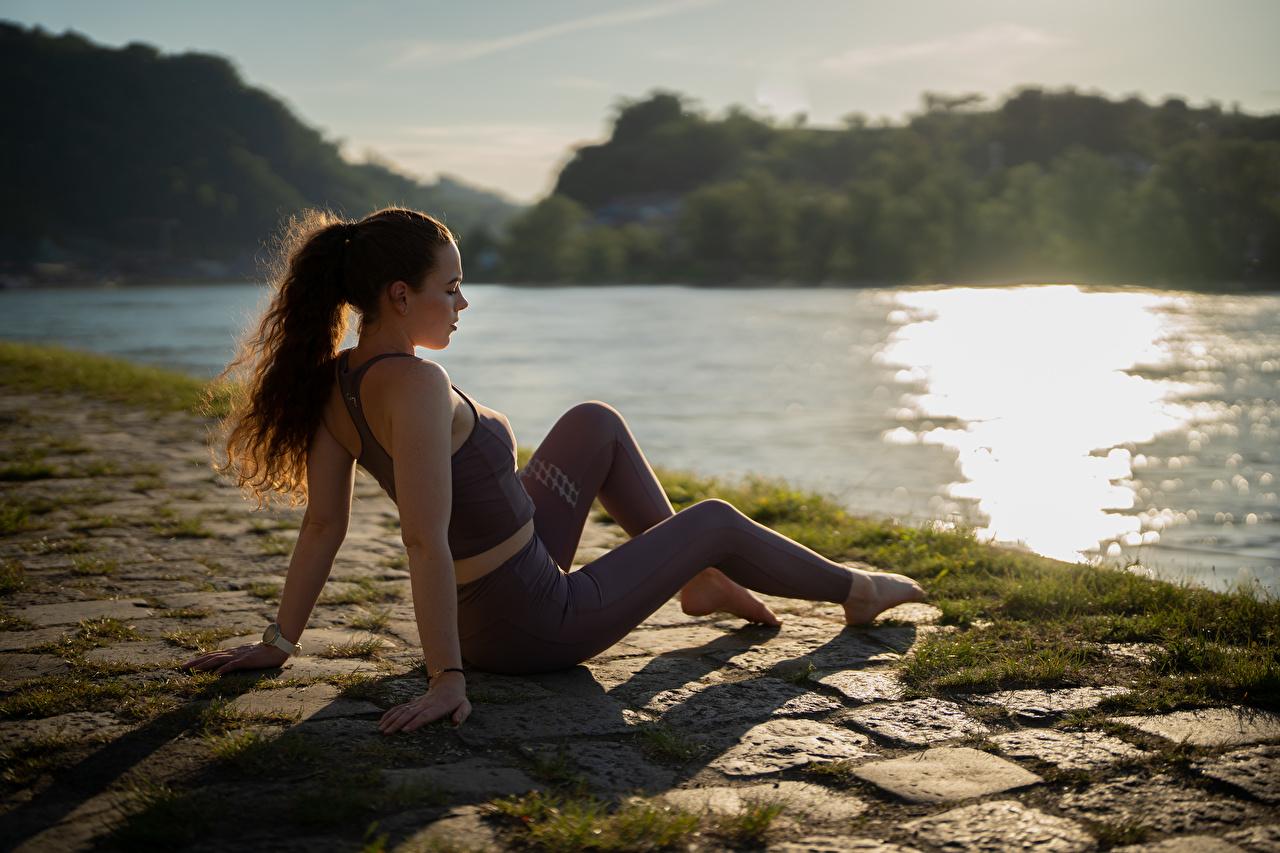Фото боке Фитнес молодые женщины ног рука Сидит Трава униформе Размытый фон девушка Девушки молодая женщина Ноги сидя Руки траве сидящие Униформа