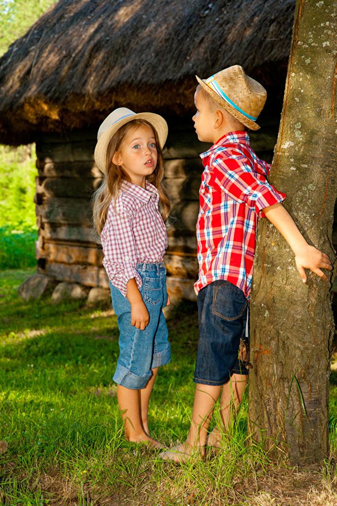 Обои Девочки Мальчики Ребёнок Двое Шляпа Джинсы Ствол дерева Дети 2 вдвоем
