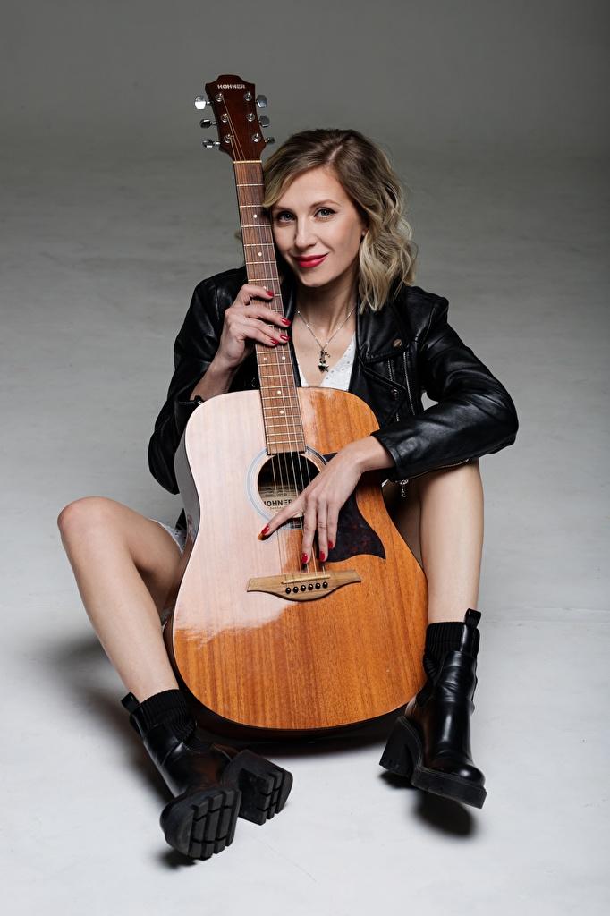 Фото блондинки гитары куртки Девушки ног сидя Серый фон Музыкальные инструменты  для мобильного телефона Блондинка блондинок Гитара с гитарой куртке Куртка куртках девушка молодая женщина молодые женщины Ноги Сидит сидящие сером фоне