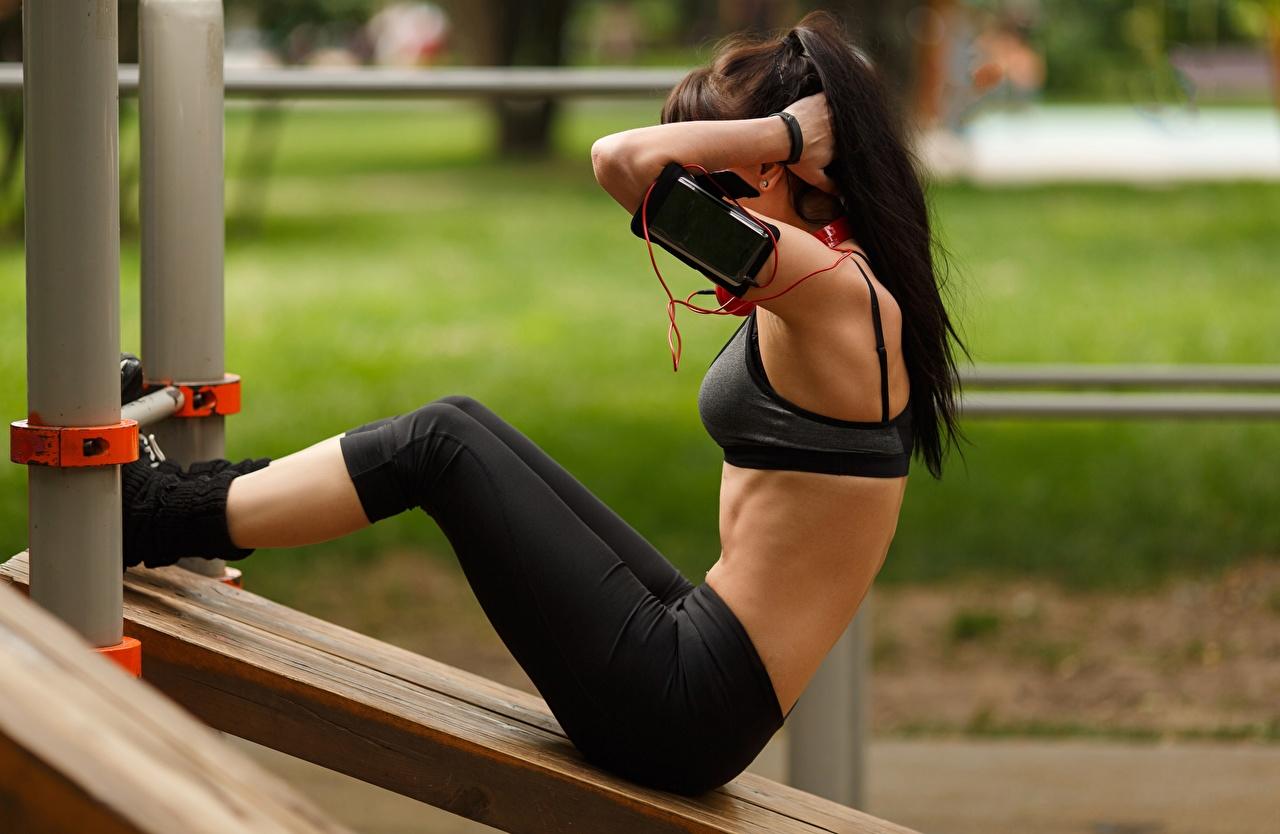 Фото Брюнетка Тренировка Смартфон позирует Фитнес Девушки спортивный Ноги Руки Сбоку брюнетки брюнеток тренируется физическое упражнение сматфоном смартфоны Поза Спорт девушка спортивные спортивная молодая женщина молодые женщины ног рука