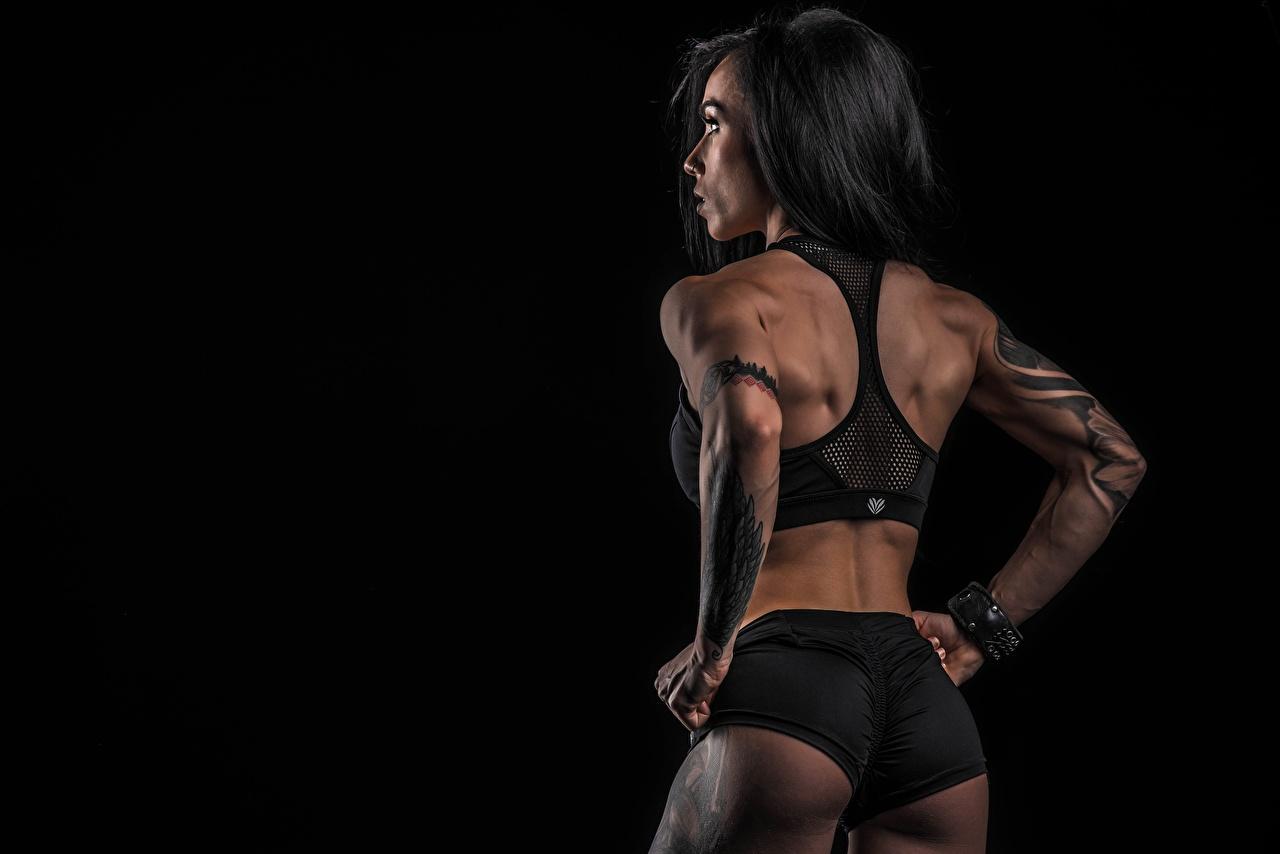 Фото Попа татуировка Поза Спина Фитнес Спорт девушка Сзади шортах на черном фоне ягодицы тату Татуировки позирует спины Девушки спортивные спортивный спортивная молодые женщины молодая женщина шорт Шорты вид сзади Черный фон