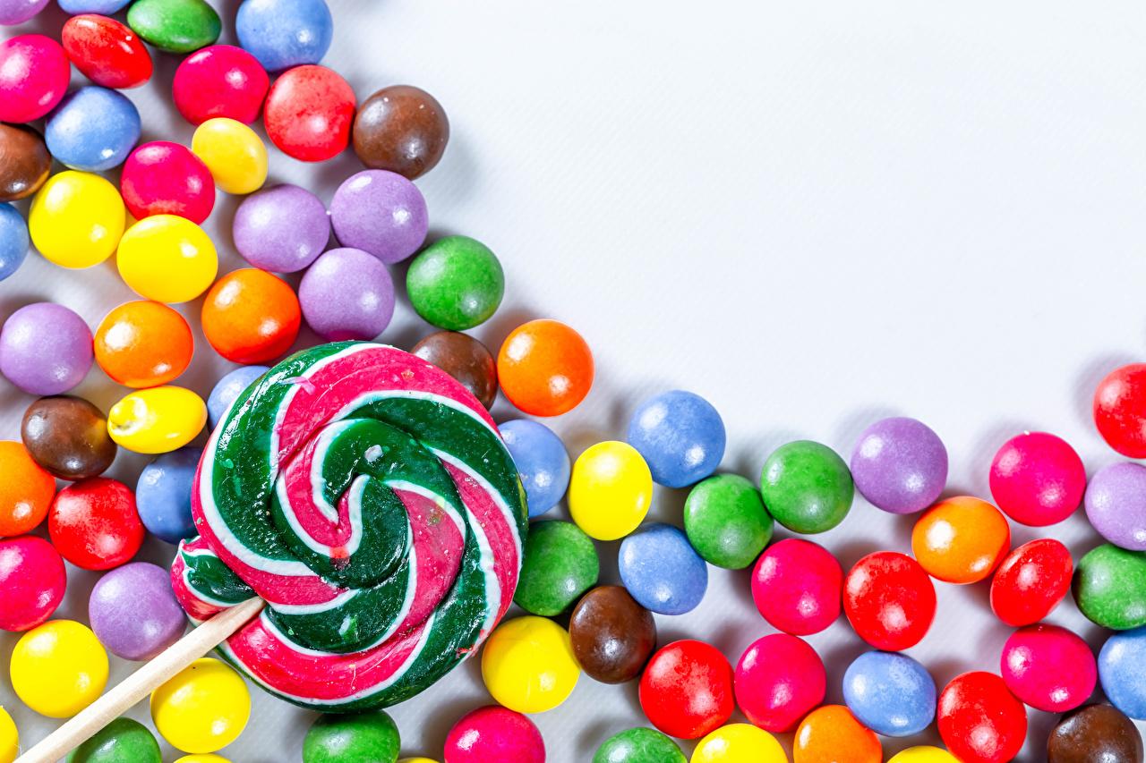 Фотографии Драже Разноцветные Леденцы Конфеты Пища белом фоне сладкая еда Еда Продукты питания Сладости Белый фон белым фоном