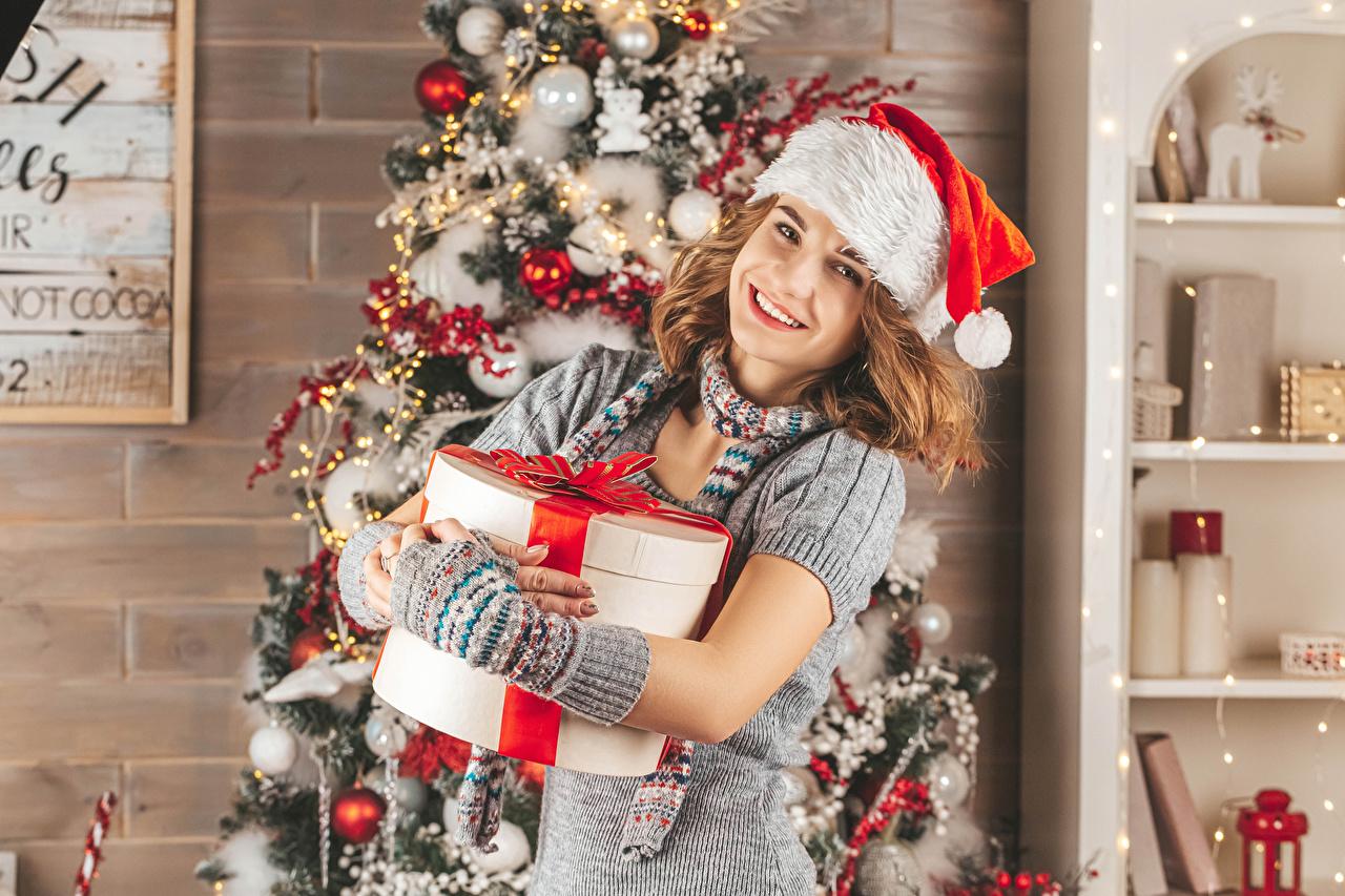 Обои для рабочего стола Шатенка Рождество Улыбка Елка шапка Девушки подарков смотрят шатенки Новый год улыбается Шапки в шапке девушка Новогодняя ёлка молодая женщина молодые женщины подарок Подарки Взгляд смотрит