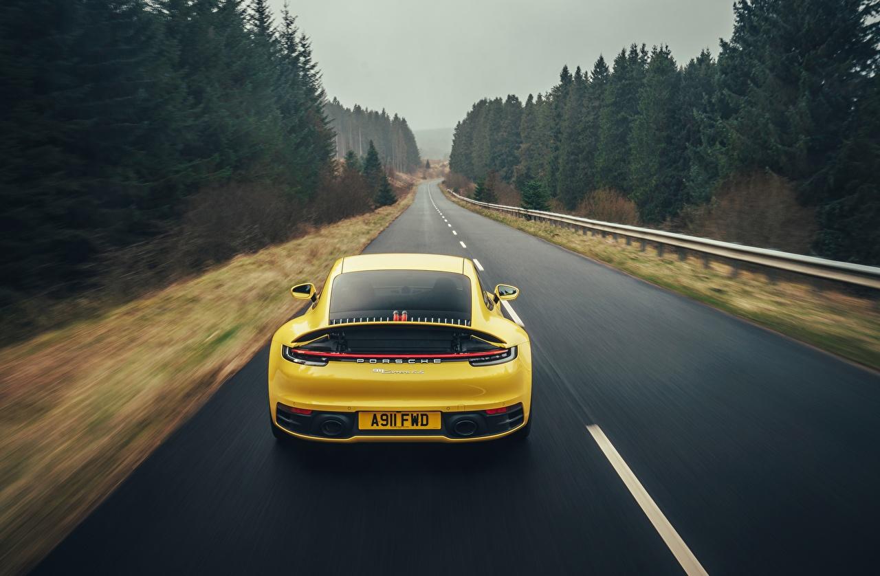 Картинки Porsche 911 Carrera 4S 2019 желтая едет Дороги машины вид сзади Порше желтых желтые Желтый едущий едущая скорость Движение авто Сзади машина автомобиль Автомобили