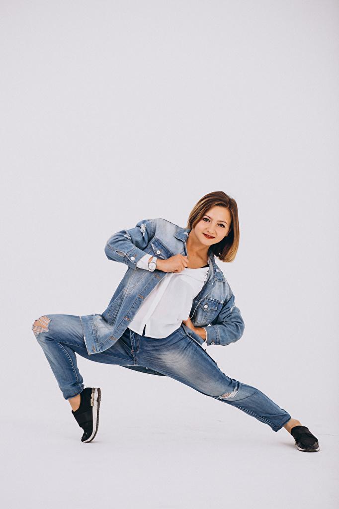 Картинка шатенки танцуют Девушки Джинсы Серый фон  для мобильного телефона Шатенка Танцы танцует девушка молодая женщина молодые женщины джинсов сером фоне