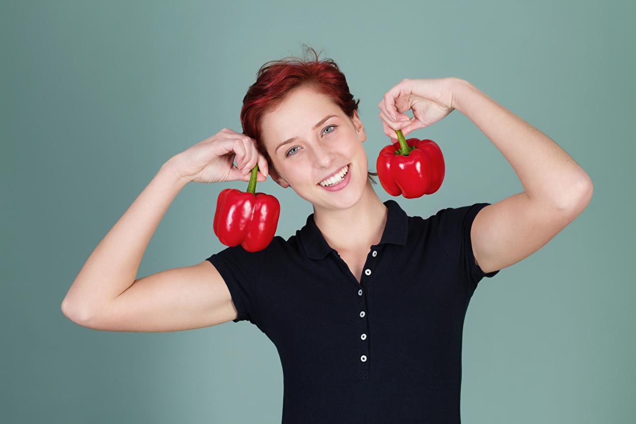 Обои для рабочего стола Рыжая Улыбка Девушки рука перец овощной Взгляд Цветной фон рыжих рыжие улыбается девушка молодые женщины молодая женщина Руки Перец смотрят смотрит