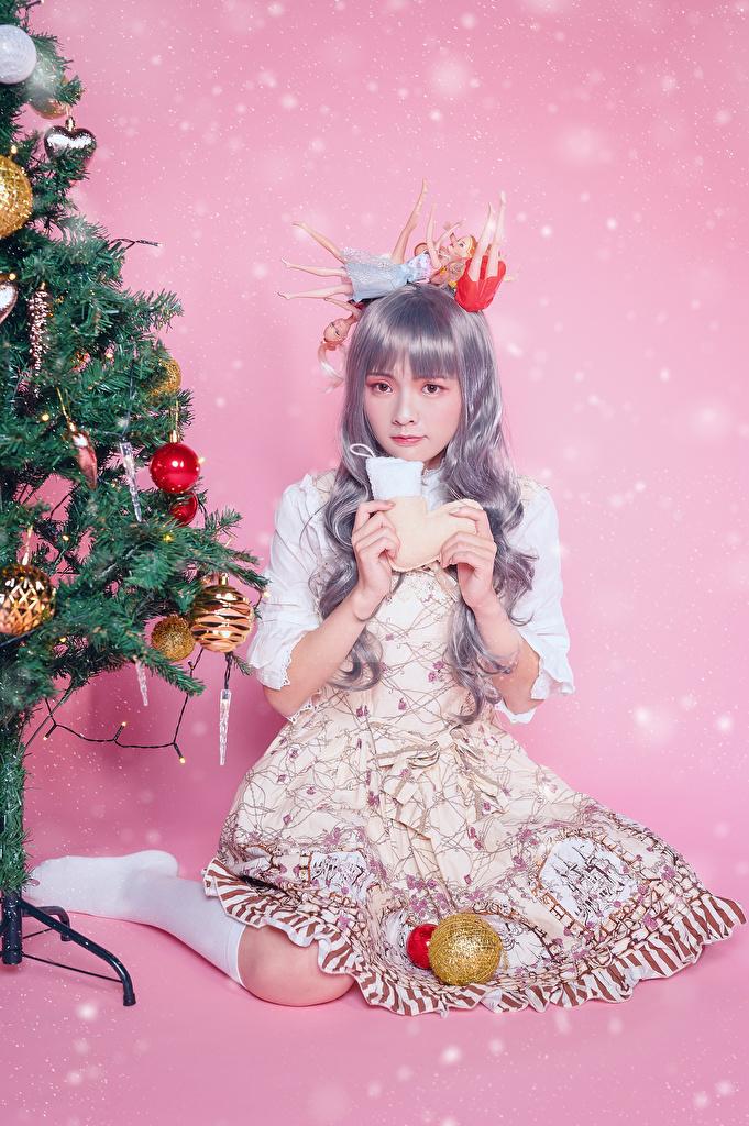 Картинка Рождество Девушки Новогодняя ёлка Азиаты Сидит Шарики смотрят Платье Цветной фон  для мобильного телефона Новый год Елка девушка молодая женщина молодые женщины азиатки азиатка Шар сидя сидящие Взгляд смотрит платья