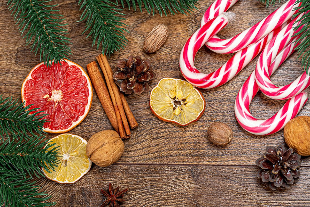 Фотография Новый год Леденцы Грейпфрут Лимоны Корица Еда Ветки Шишки Орехи Доски Рождество Пища шишка ветка ветвь на ветке Продукты питания