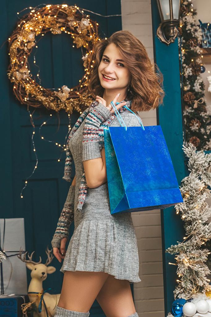 Фотография шатенки Рождество Улыбка молодые женщины подарок смотрит платья  для мобильного телефона Шатенка Новый год улыбается девушка Девушки молодая женщина Подарки подарков Взгляд смотрят Платье