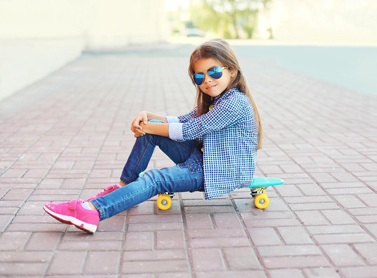 Картинка Девочки ребёнок рубашке джинсов Скейтборд очков сидящие девочка Дети рубашки Рубашка Джинсы Роликовая доска Очки сидя очках Сидит