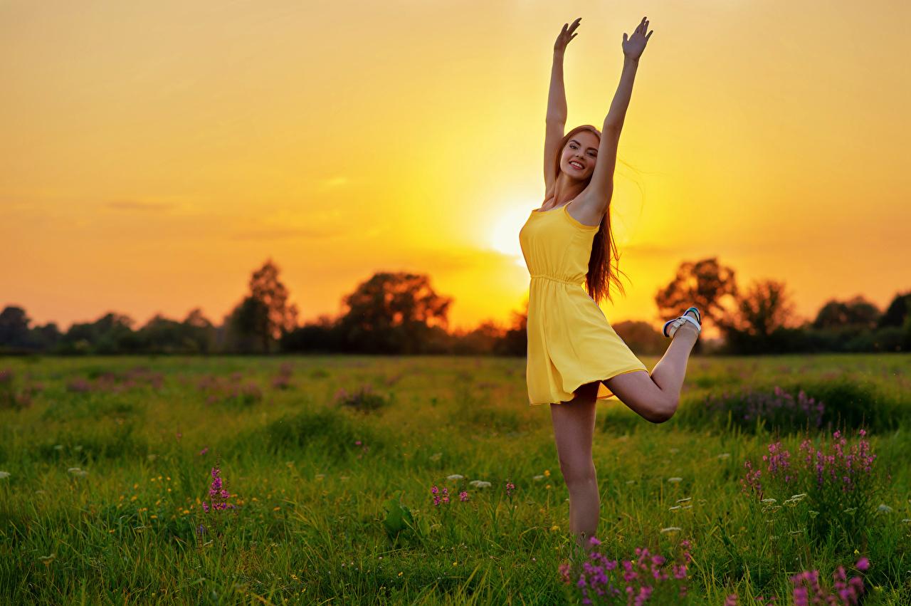 Фотография Улыбка Поза девушка Ноги Луга Рассветы и закаты рука траве платья улыбается позирует Девушки молодые женщины молодая женщина ног рассвет и закат Руки Трава Платье