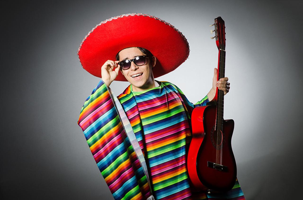 Фотография Мужчины с гитарой Улыбка шляпы очках Серый фон Гитара гитары мужчина улыбается шляпе Шляпа Очки очков сером фоне
